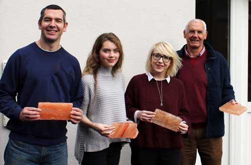 Four people holding salt blocks